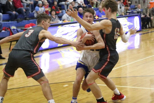 Ontario's Griffin Shaver goes through two Shelby defenders for the layup during the Warriors' win over Shelby on Wednesday night.