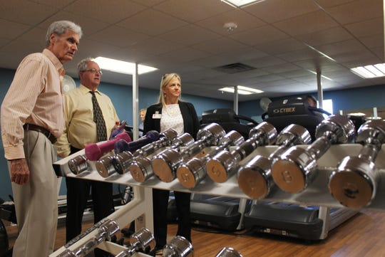 Past Y board presidents Ernie Bretzmann and Craig Woodward (yellow shirt) enjoy a tour of the fitness facility with CEO Cindy Love-Abounader after the luncheon.