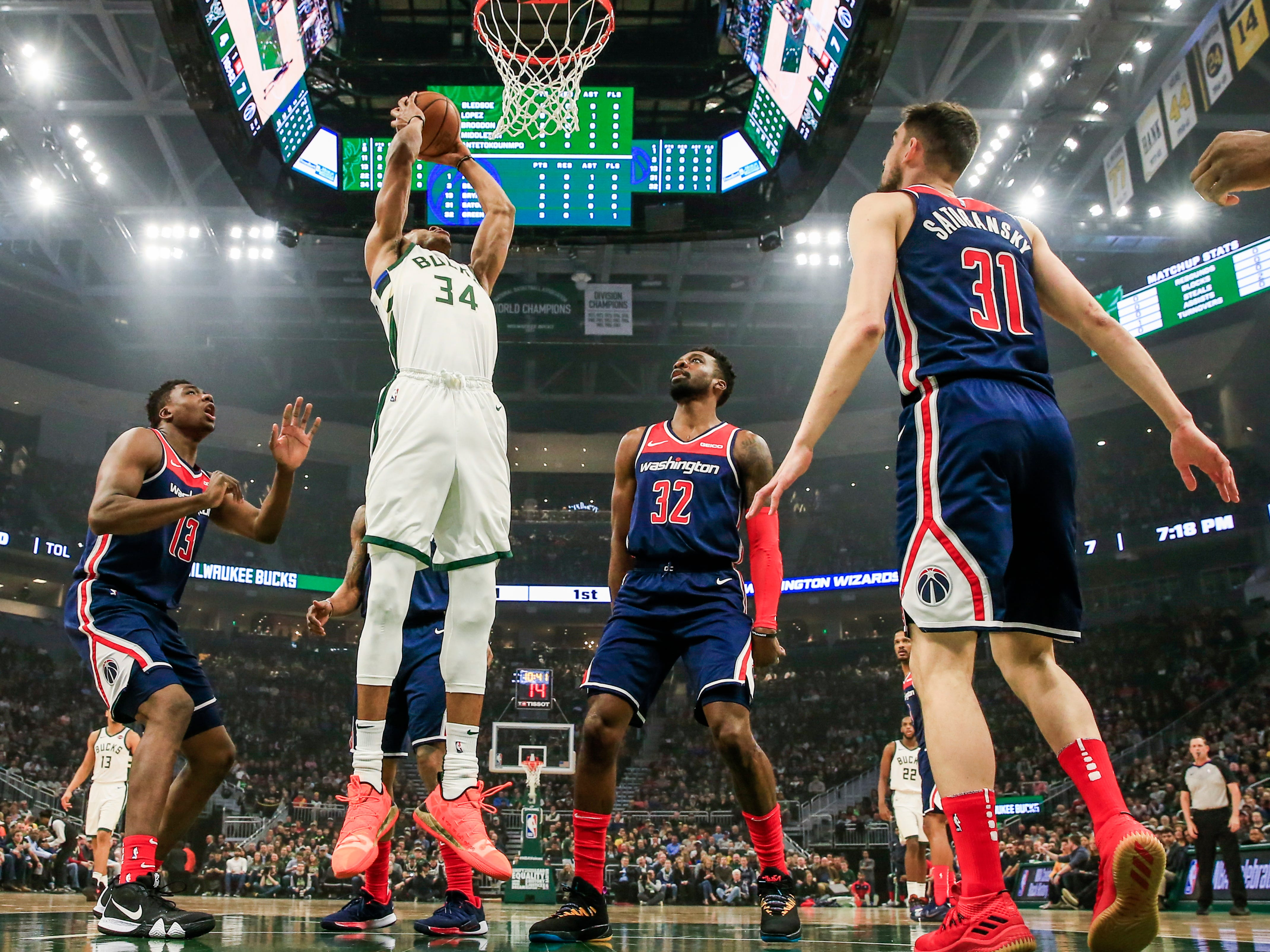 Giannis Antetokounmpo of the Bucks goes up for a shot by the basket as a quartet of Wizards defenders just stand there and watch during the first half Wednesday.