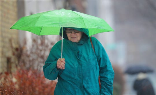 Erin McGovern of Milwaukee walks with her umbrella in the rain down North Cass Street just south of East Kilbourn  Avenue on the way to her home after a doctor appointment in Milwaukee on Thursday, Feb. 7, 2019.