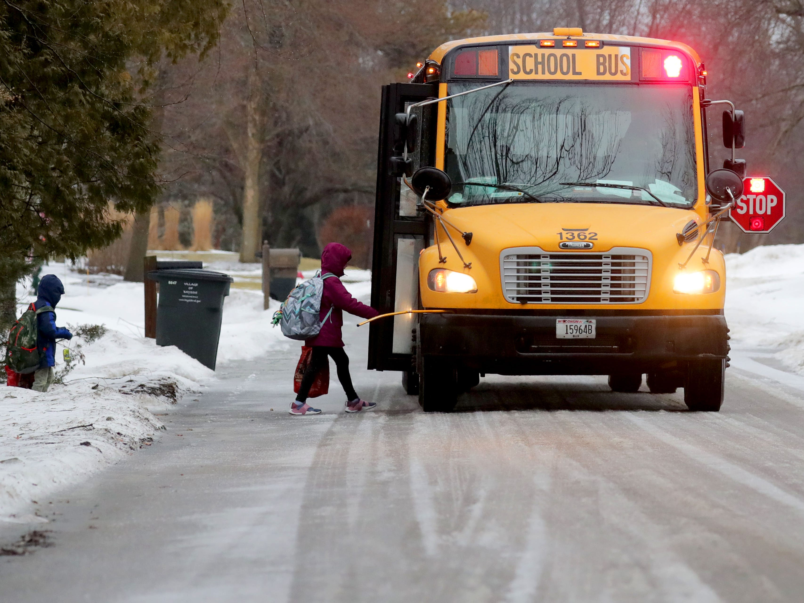 A child boards a school bus on an icy North Bayside Drive in Bayside on Wednesday, Feb. 6, 2019. While freezing rain made roads and sidewalks a slushy mess Wednesday, the Milwaukee metro area is in for another round of icy weather that is expected to make the commutes hazardous Wednesday night and Thursday morning. A winter weather advisory for Ozaukee and Washington counties as well as the Madison area has been issued for 6 p.m. Wednesday to 6 p.m Thursday. Total snow accumulations of up to 2 inches and ice accumulations of two-tenths to three-tenths of an inch are expected.