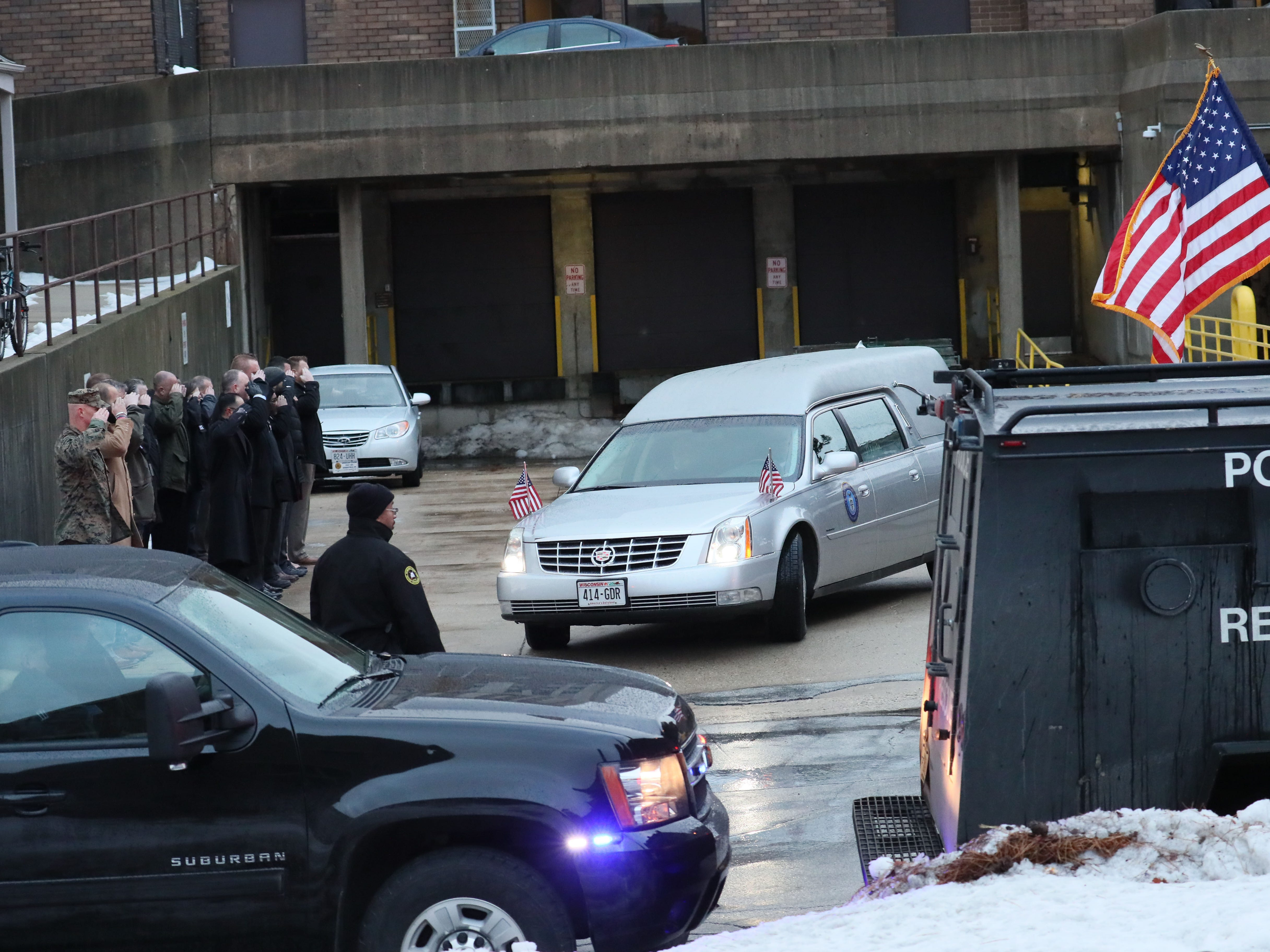 After the flag is draped over the coffin of slain Officer Matthew Rittner it was loaded into a hearse at the Milwaukee County Medical Examiners office and the vehicle joined the police motorcade to the funeral home.