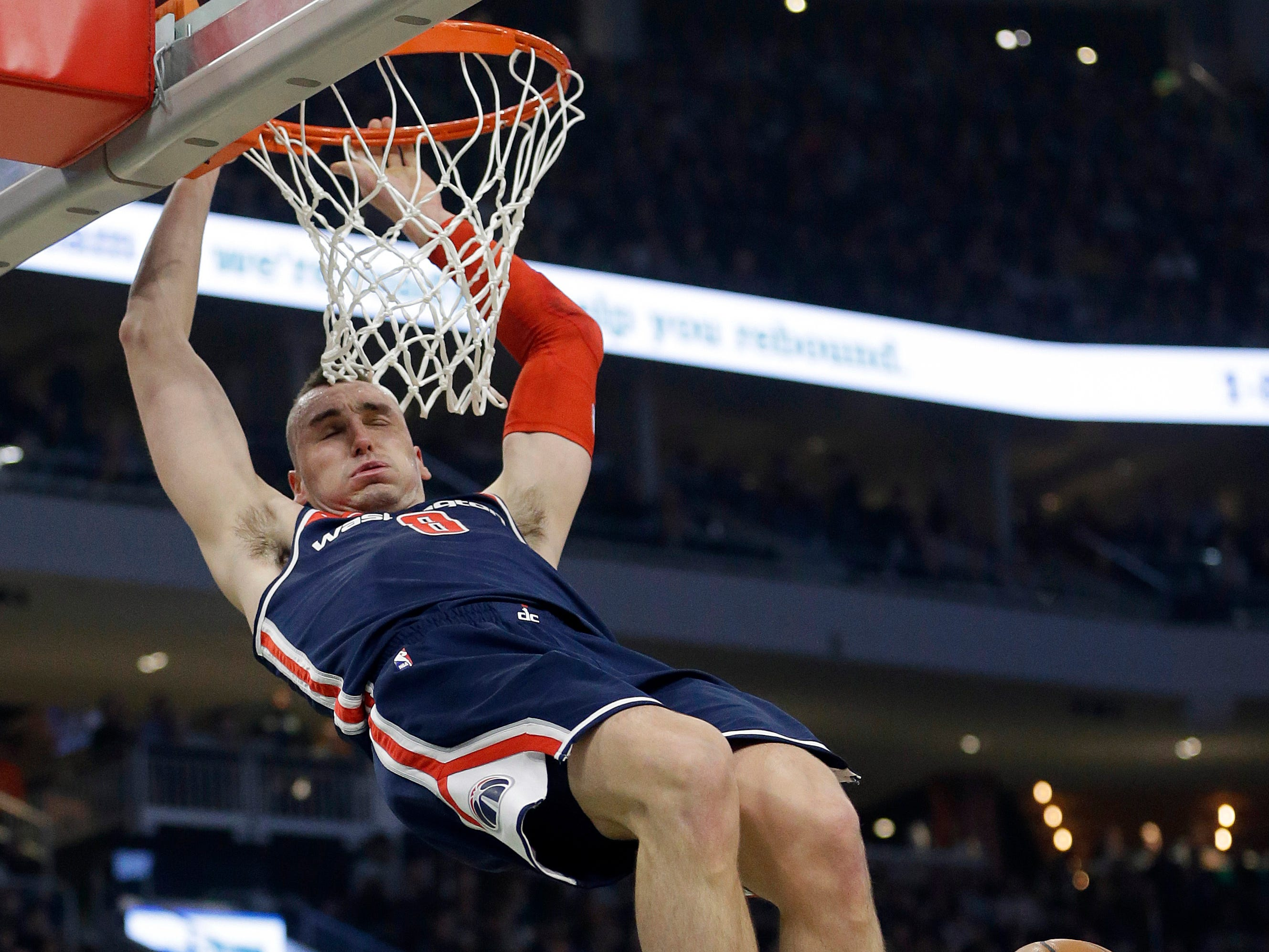Sheboygan's own Sam Dekker of the Wizards hangs on the rim after throwing down a dunk against the Bucks during the first half on Wednesday.