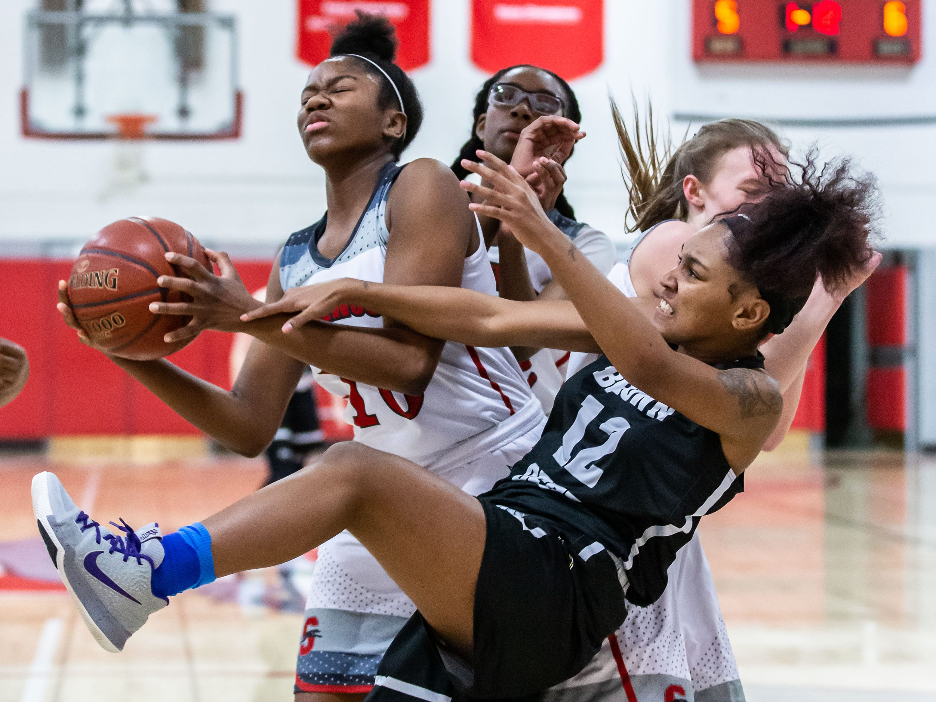 Shorewood's Ta'Niya Robinson (left) battles for a rebound with Brown Deer's Olivia Sellers (12) during the game at Shorewood on Wednesday, Feb. 6, 2019.
