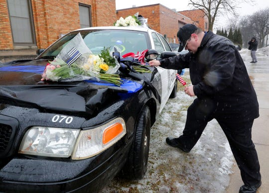 """I've had to do this three times in the last eight months,"" said Timothy Nelson of Oak Creek as he places small flags in a bouquet near a squad car adorned with flowers as a memorial for fallen Milwaukee Police Officer Matthew Rittner at the Neighborhood Task Force police building, 4715 W. Vliet St., in Milwaukee on Thursday.  Rittner was shot and killed Wednesday morning by a suspect wanted on drug and gun offenses in the 2900 block of South 12th Street in Milwaukee."