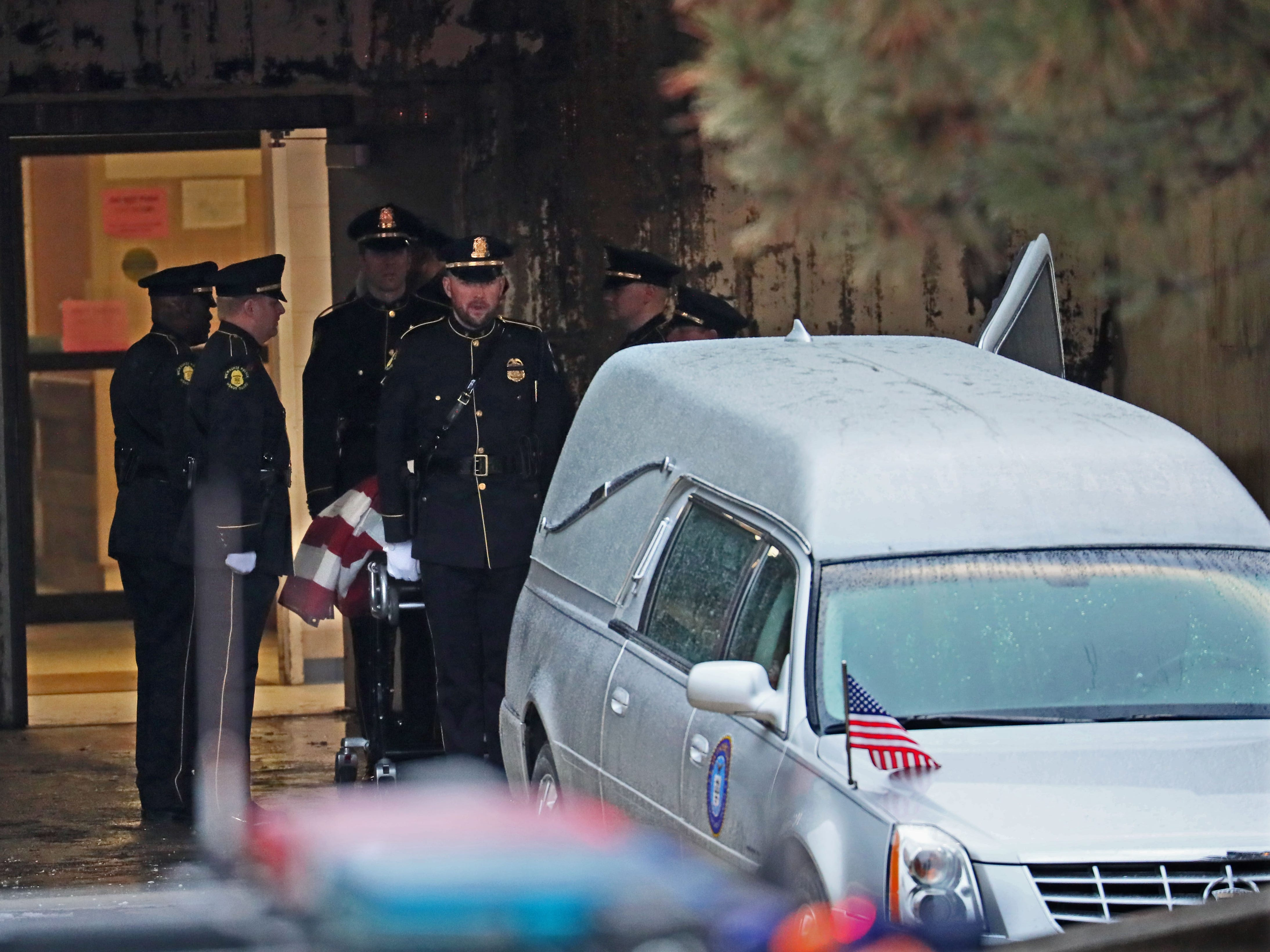 A Police honor guard loads the flag draped coffin of Officer Matthew Rittner into a waiting hearse at the Milwaukee County Medical Examiners office to be taken to the funeral home.