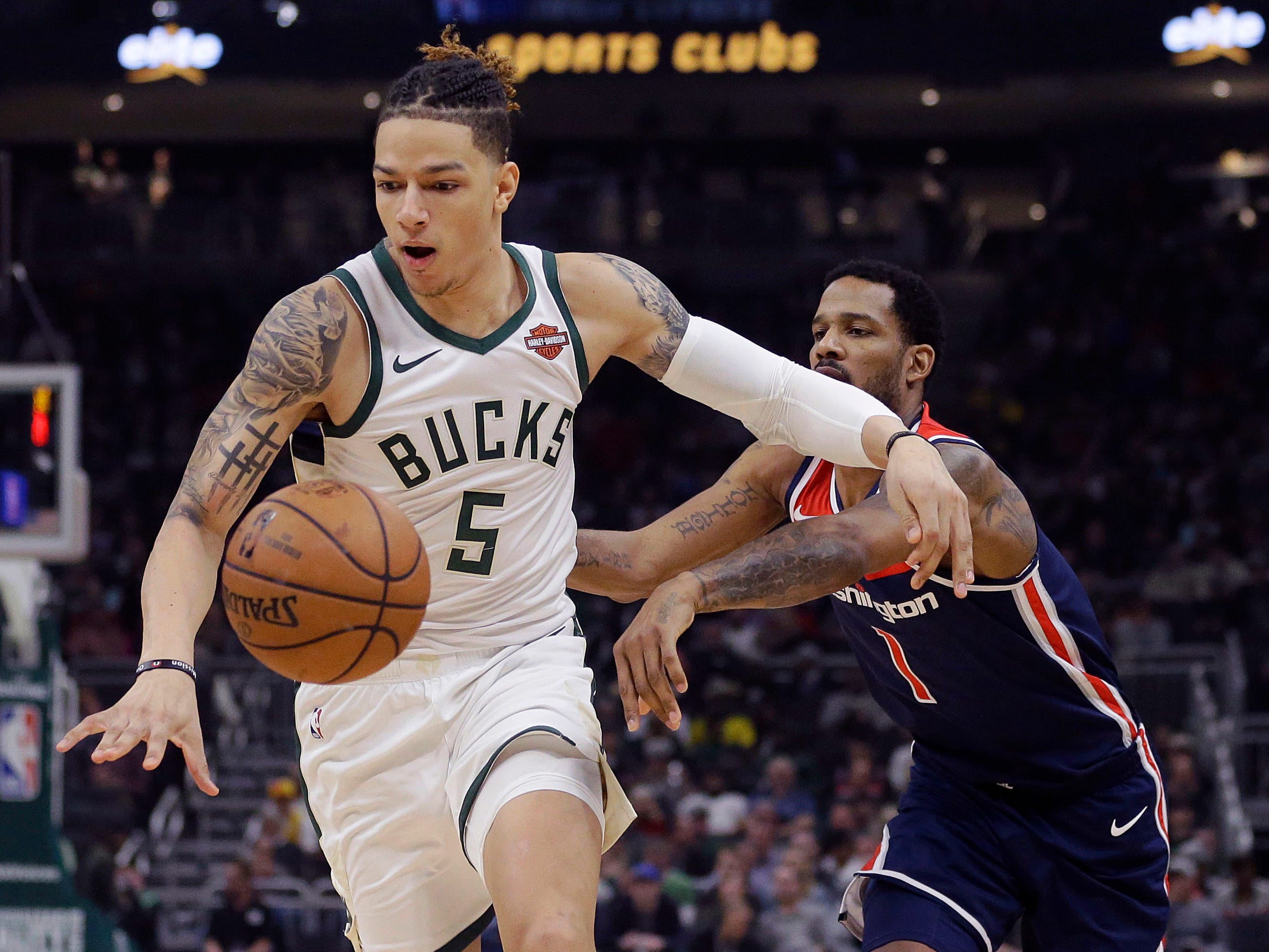 Bucks forward D.J. Wilson gets to a loose ball ahead of  Trevor Ariza of the Wizards during the first half Wednesday.
