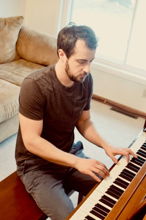 """Dan Kolesari plays the piano at home in Brookfield. His third album, """"A Shot in the Dark"""" will be released March 1."""