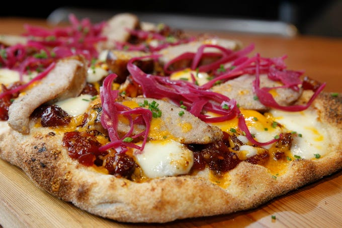 Twisted Fire makes a variety of pinsas in its wood-fired pizza oven. The Wisconsin flatbread is topped with cherry chutney, Hook's 5-year cheddar, grilled bratwurst, cheese curds and pickled red cabbage; the dough is allowed to develop for three days before its baked.