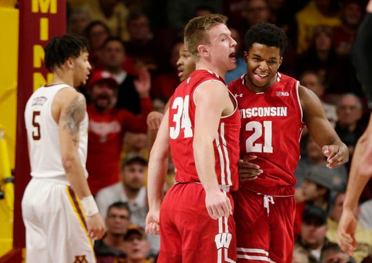 Wisconsin guard Brad Davison (34) yells to forward Kahlil Iverson after Iverson dunked and was fouled, while Minnesota guard Amir Coffey (5) stands nearby, during the first half of an NCAA college basketball game Wednesday, Feb. 6, 2019, in Minneapolis. (AP Photo/Andy Clayton-King) ORG XMIT: MNAK105