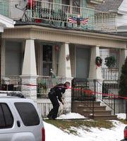 A Milwaukee police officer ducks under crime scene tape Thursday at 2945 S.  12th St.