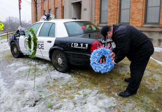 """I've had to do this three times in the last eight months,"" said Timothy Nelson, of Oak Creek as he places small flags in a bouquet near a squad car adorned with flowers as a memorial for fallen Milwaukee police officer, Matthew Rittner in front of the old District 3 station on West Vliet Street that now serves as a home for the department's speciality units in Milwaukee on Thursday, Feb. 7, 2019. Rittner was shot and killed Wednesday morning in an exchange of gunfire with a suspect wanted on drug and gun offenses on Wednesday the 2900 block of South 12th Street in Milwaukee.    Photo by Mike De Sisti / Milwaukee Journal Sentinel"