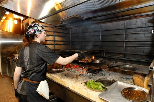 Twisted Fire sous chef Kaitlin Schleef cooks over a fire at the restaurant's custom-made open hearth. Some element of nearly every dish on the menu is made at the hearth, said chef Jason Joyner. The restaurant also has a wood-fired pizza oven.