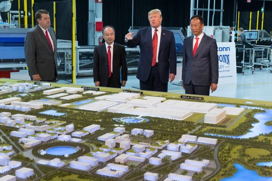 President Trump, Softbank CEO Masayoshi Son (second from left) and Foxconn Chairman Terry Gou examine a model of the factory being developed during the ceremonial groundbreaking for Foxconn's factory in Mount Pleasant.