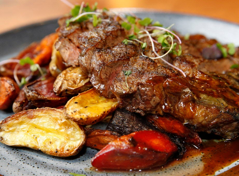 Wood-grilled rib-eye is sliced and served with charred onion butter, roasted fingerling potatoes, carrots and demi-glace at Twisted Fire.