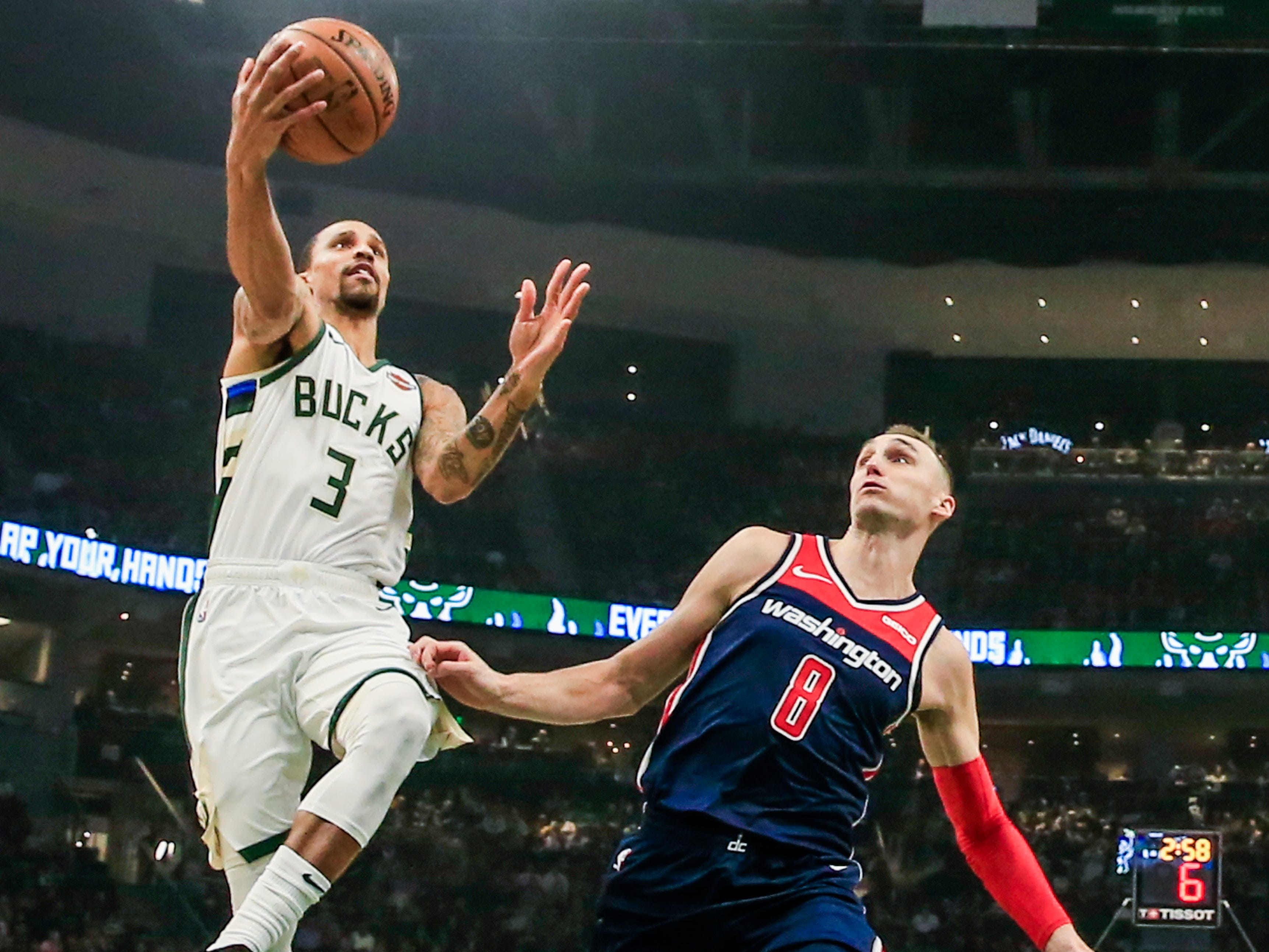 Bucks guard George Hill gets to the basket for a shot past Wizards forward Sam Dekker on Wednesday night.
