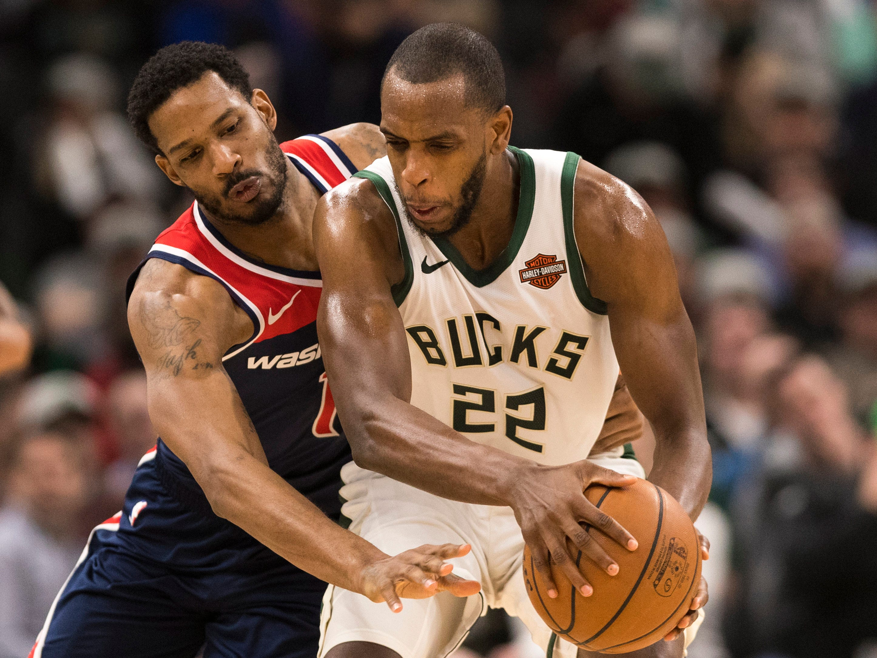 Bucks forward Khris Middleton protects the ball from the prying hands of Wizards forward Trevor Ariza during the third quarter Wednesday.
