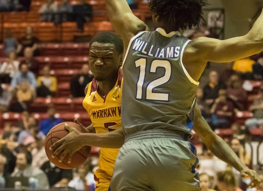 University of Louisiana at Monroe's Daishon Smith (5) drives into Georgia State's defending Kane Williams (12) during the game at Fant-Ewing Coliseum on Feb. 6.