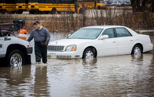 Northwest Towing responds to a call regarding a vehicle stranded in flood water on N. Elgin Street Thursday afternoon.
