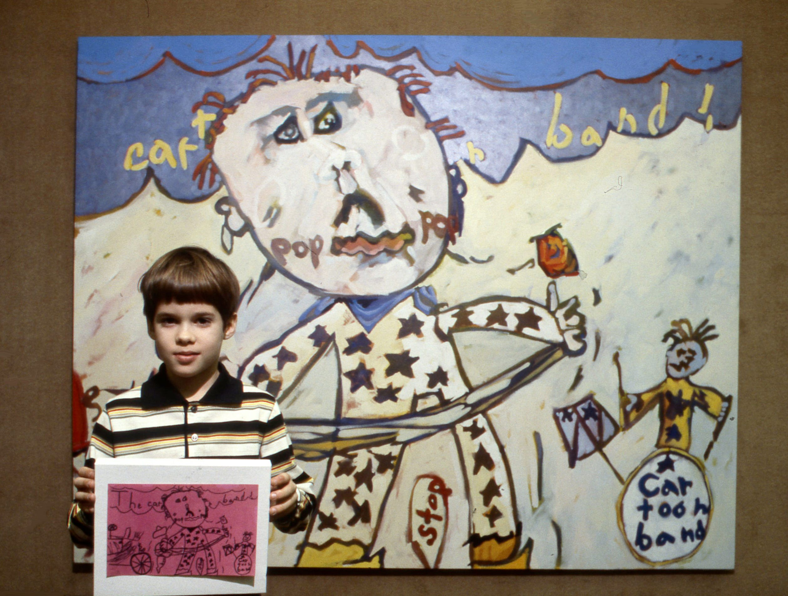 "Andy Hochstetler, 9, holds his drawing of ""Cartoon Band,"" from which his father, Max Hochstetler, made the large painting behind him Feb. 6, 1979. Both works are in the show ""Images from My House"" at Austin Peay State University's Trahern Gallery in Clarksville."