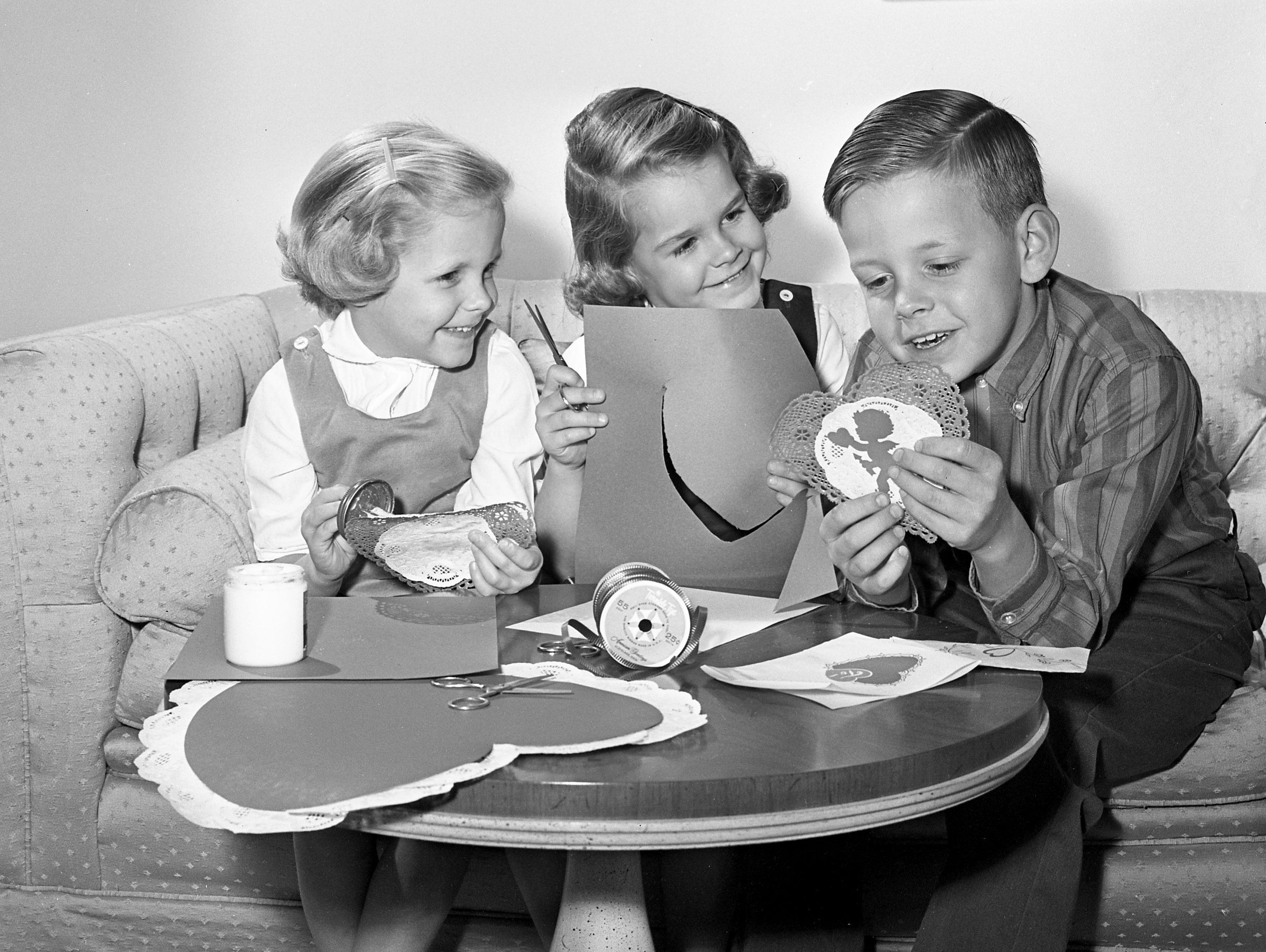 Claire, left, and Ellen Miller look at their brother, Ric, as he reads a verse on the Valentine they are making their mother, Mrs. Richard Miller, Feb. 6, 1964.