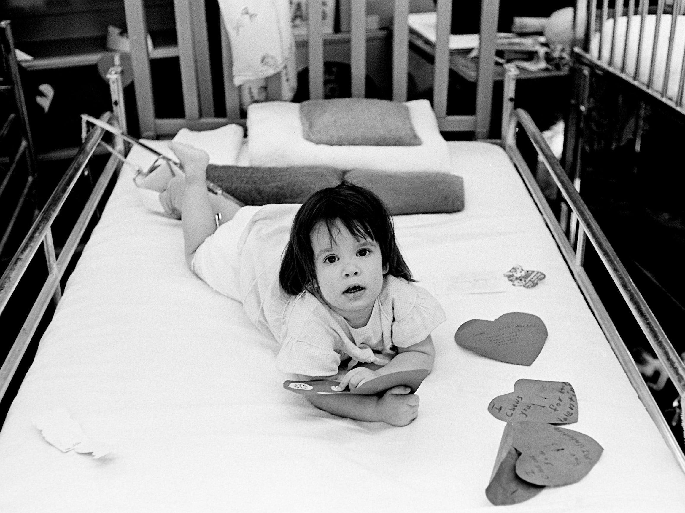 Beth Bentley, 20-month-old patient from Gainesboro, admires one of her Valentine cards during a party Feb. 14, 1963, at the Junior League Home for Crippled Children in Nashville.
