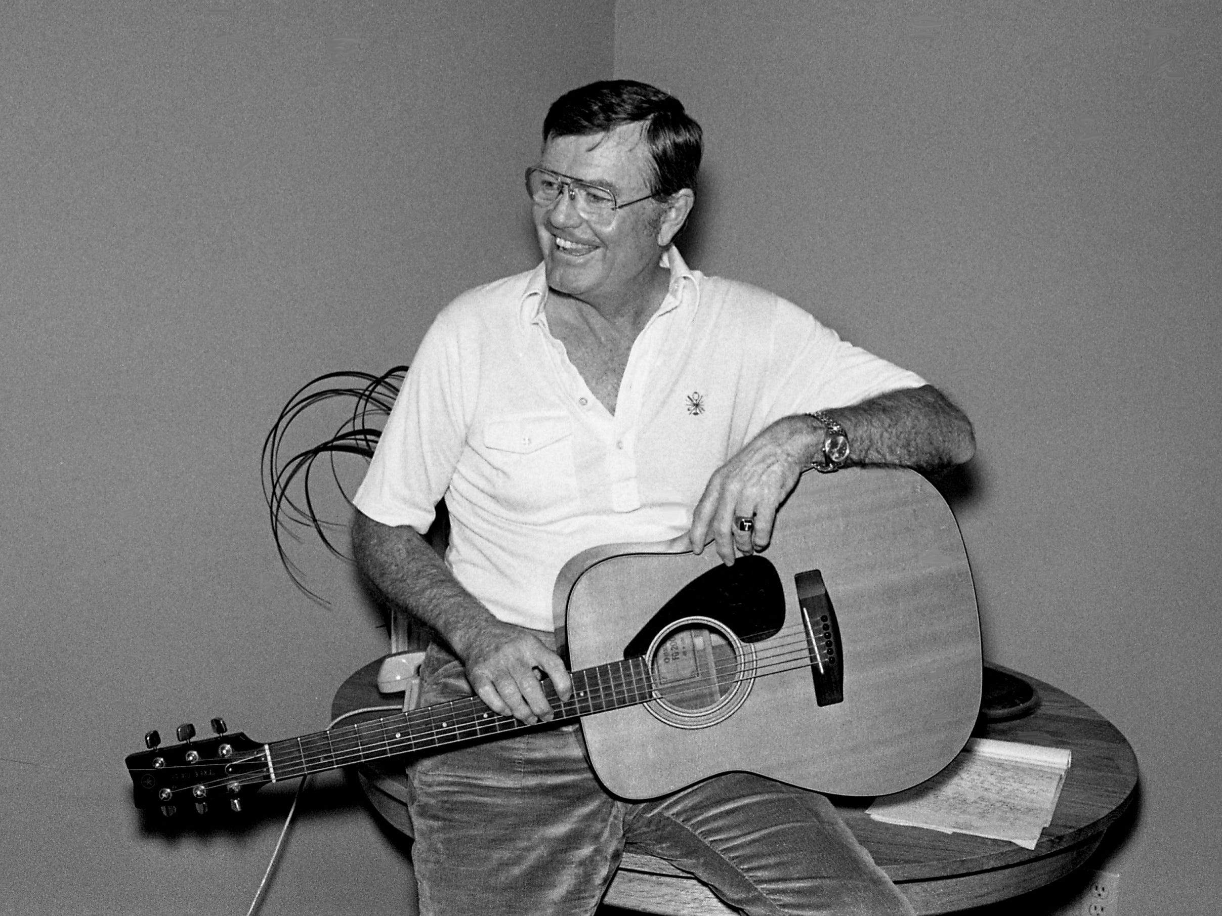 University of Texas athletic director and former head coach Darrell Royal relaxes with a guitar at the offices of Tree Publishing Co. on Feb. 23, 1979. Royal was in town for a visit to the Nashville Songwriters Awards banquet.
