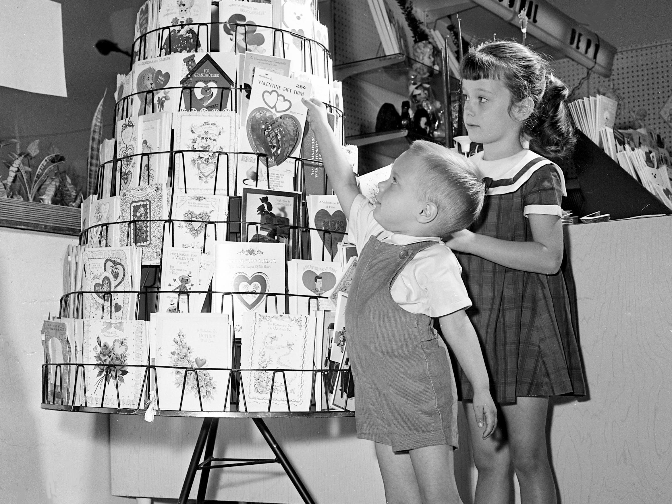 Selecting his special Valentine is William J. Elliston III, who is getting assistance from his sister, Elizabeth, at a local store Feb. 6, 1964.