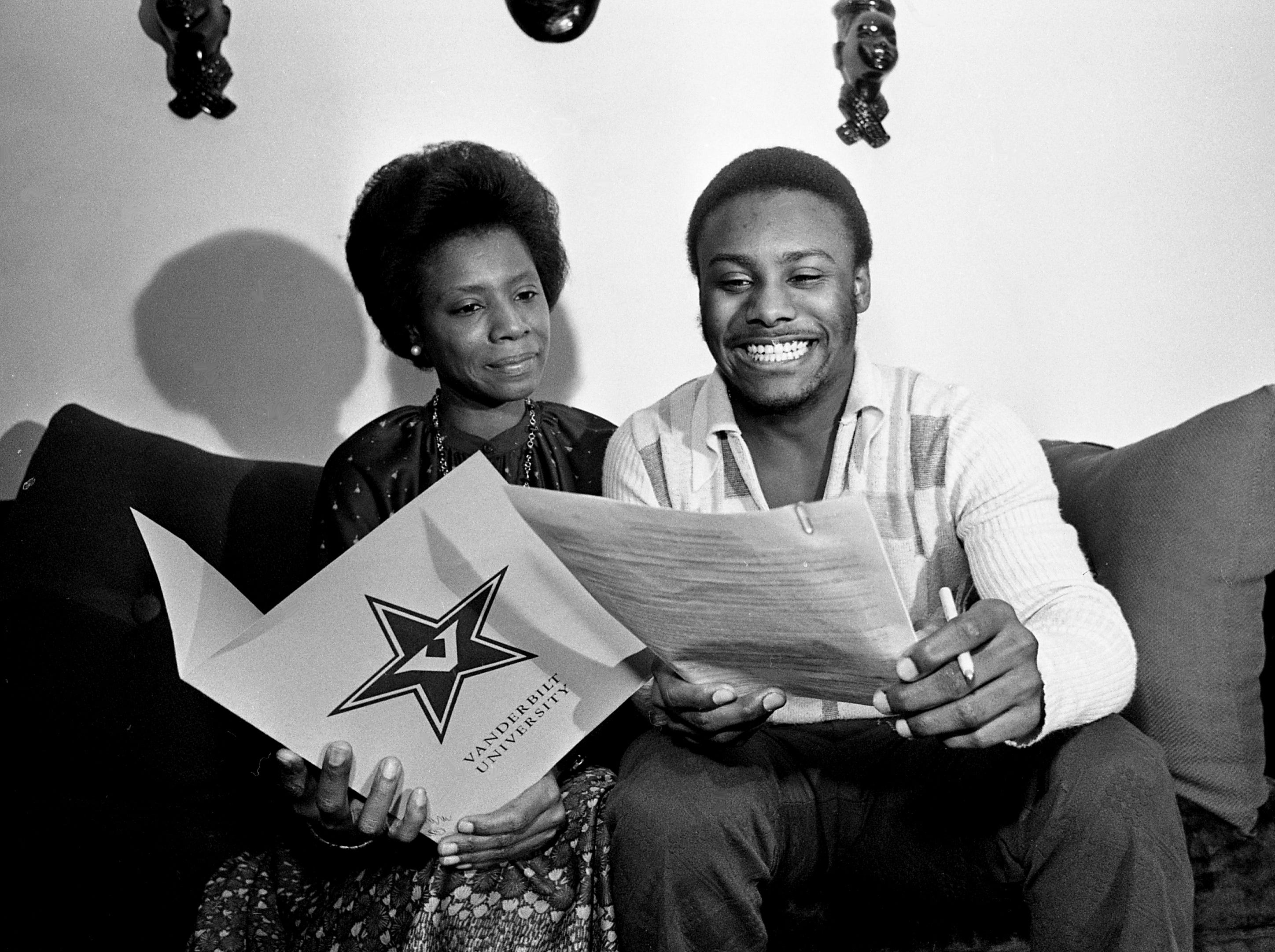 With his mother at his side, Hillsboro High star running back Lucius High looks over the grant he signed at home Feb. 9, 1979, to become the 23rd recruit for Vanderbilt University new head football coach George MacIntyre. High ranked as the NIL's second-leading rusher for a career of 3,401 yards in three years, just 53 behind record-holder Preston Brown of Maplewood, now a member of Vanderbilt.