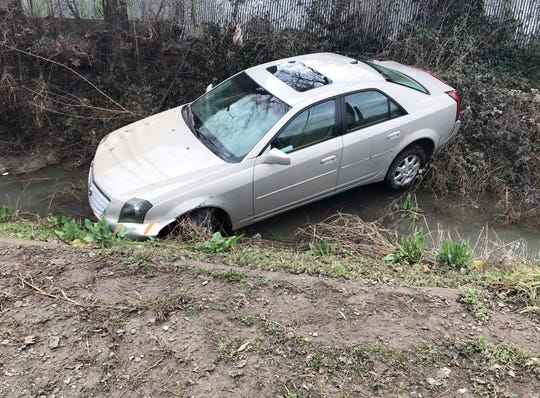 A car rests in a stream behind AMS Auto Sales and Repair on Nolensville Road after heavy rains hit Middle Tennessee overnight Thursday, Feb. 7, 2019, in Nashville, Tenn.