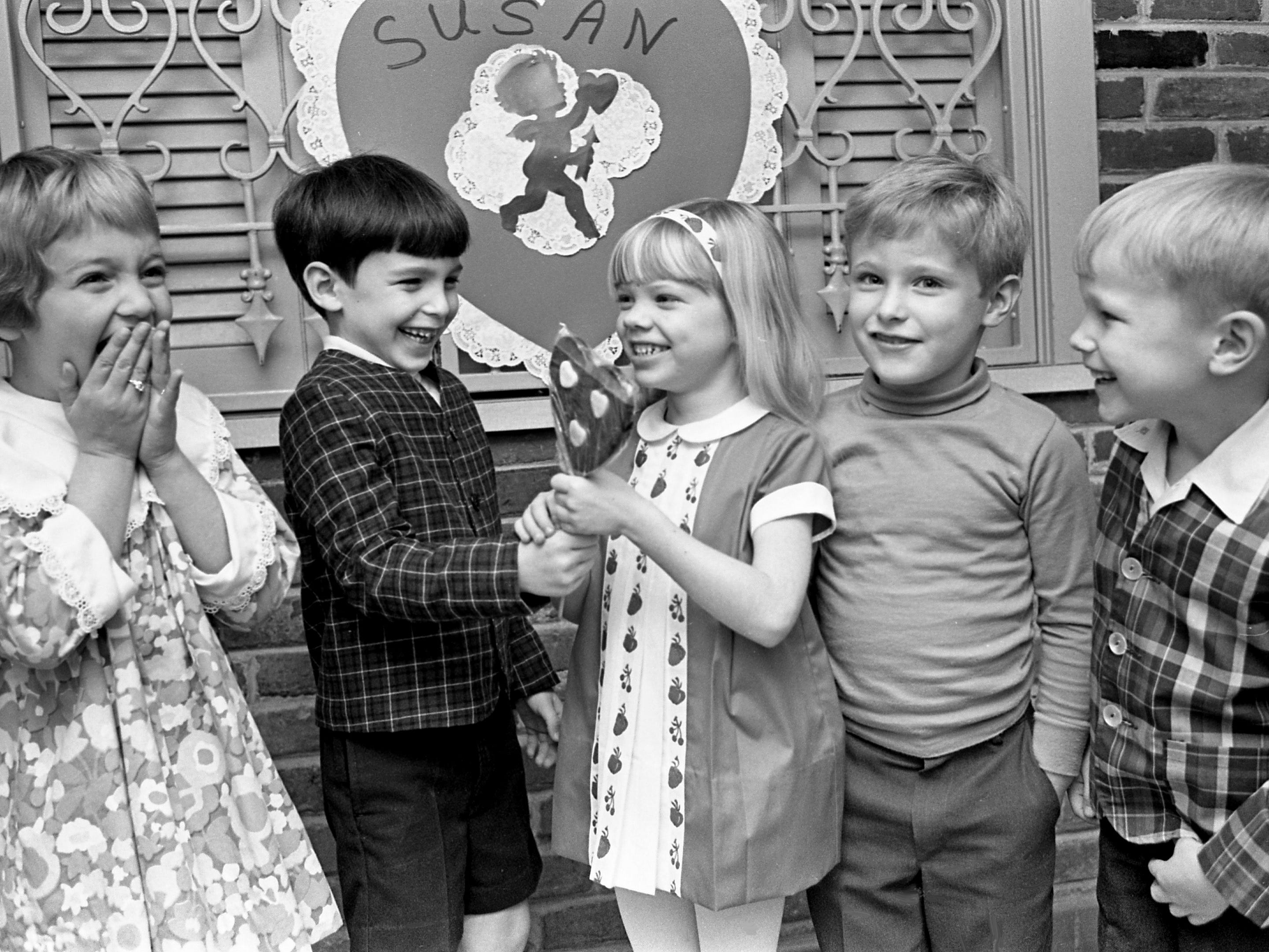 Susan Shreeve, center, was guest of honor at a Valentine party given by her mother, Mrs. George Shreeve, at the Seven Hills Club on Feb. 8, 1968. Susan is receiving a valentine gift from Tim Werthan, second from left, as Joan Richard, left, Taft Garrett and Johnny Mills look on.