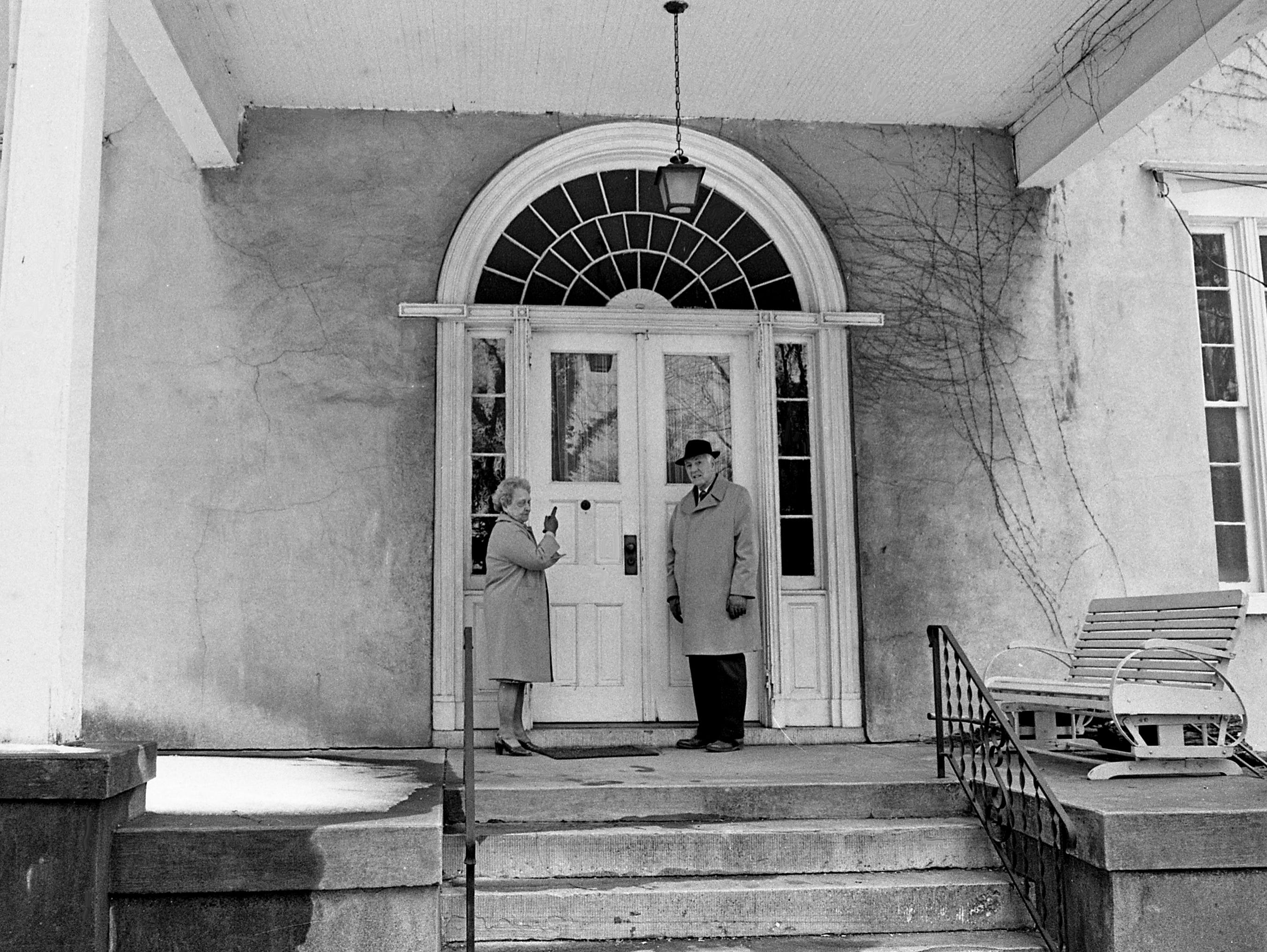 Mrs. Howard A. Moore, left, owner of the Woodlawn, points out the distinctive architectural feature of the huge fanlight over the original entrance to Terry Hart on Feb. 20, 1979. Hart is a descendant of the original owner.