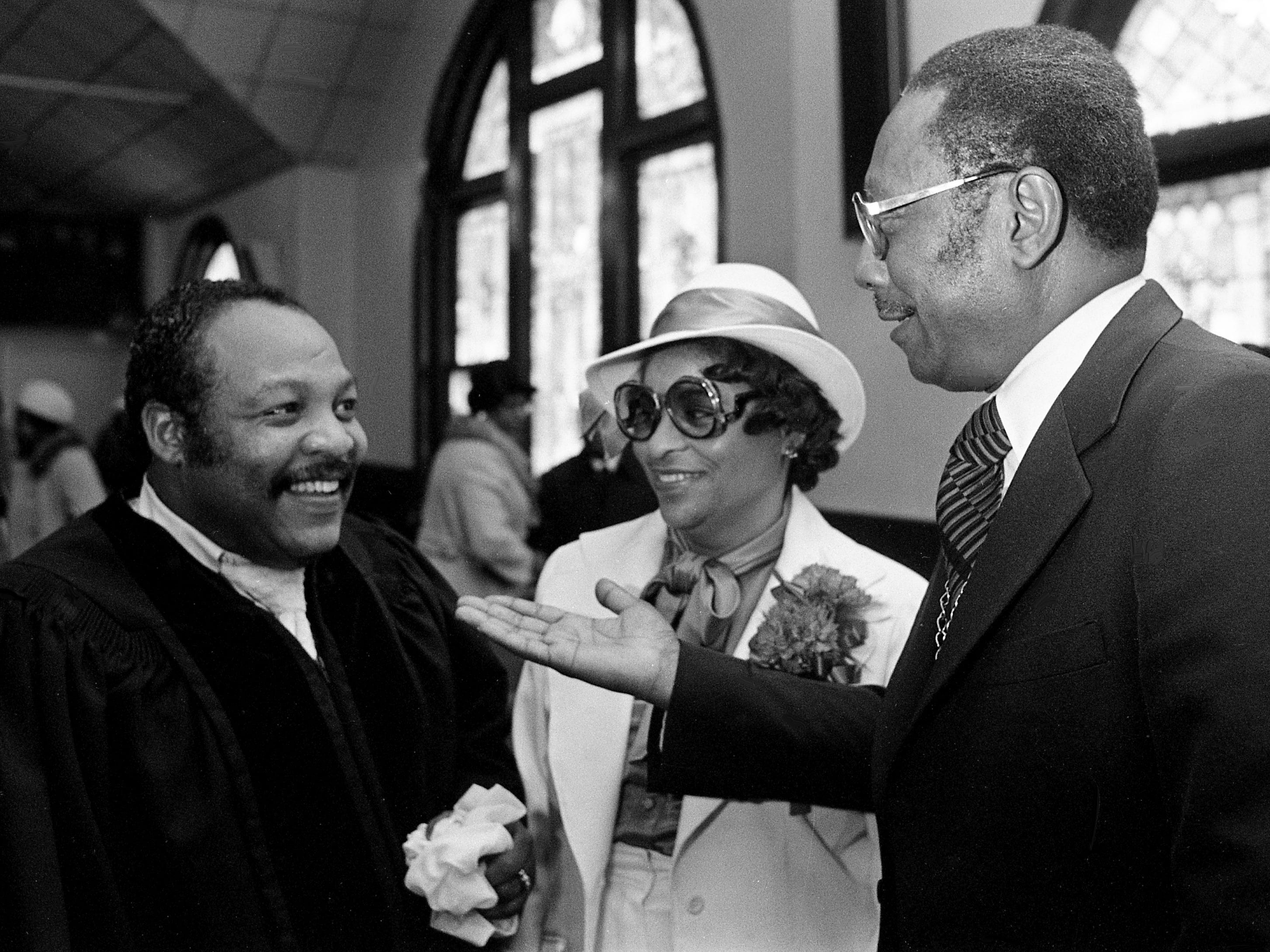 The Rev. William H. Ryan Jr., left, guest speaker at Mount Zion Baptist Church, congratulates the church pastor, the Rev. E.W. Roberson, right, on his seventh anniversary there as Mrs. Roberson looks on Feb. 25, 1979.
