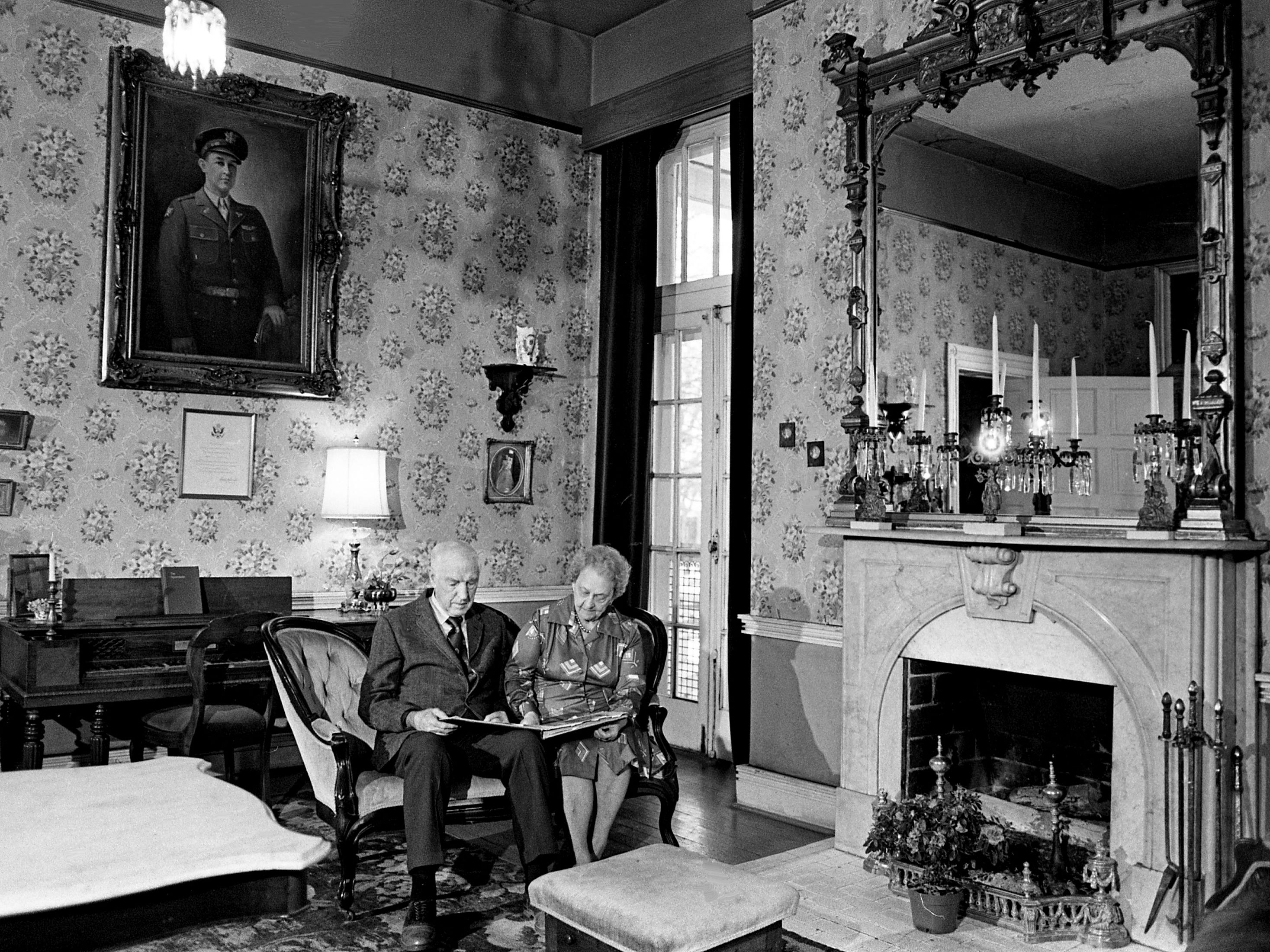 In the parlor of the Woodlawn, owner Mrs. Howard A. Moore, left, looks through a scrapbook on the history of the house Feb. 20, 1979, with Terry Hart, descendant of Capt. John Nichols, who built the house in 1812. The home at 127 Woodmont Blvd. has recently been placed on the National Register of Historic Places.