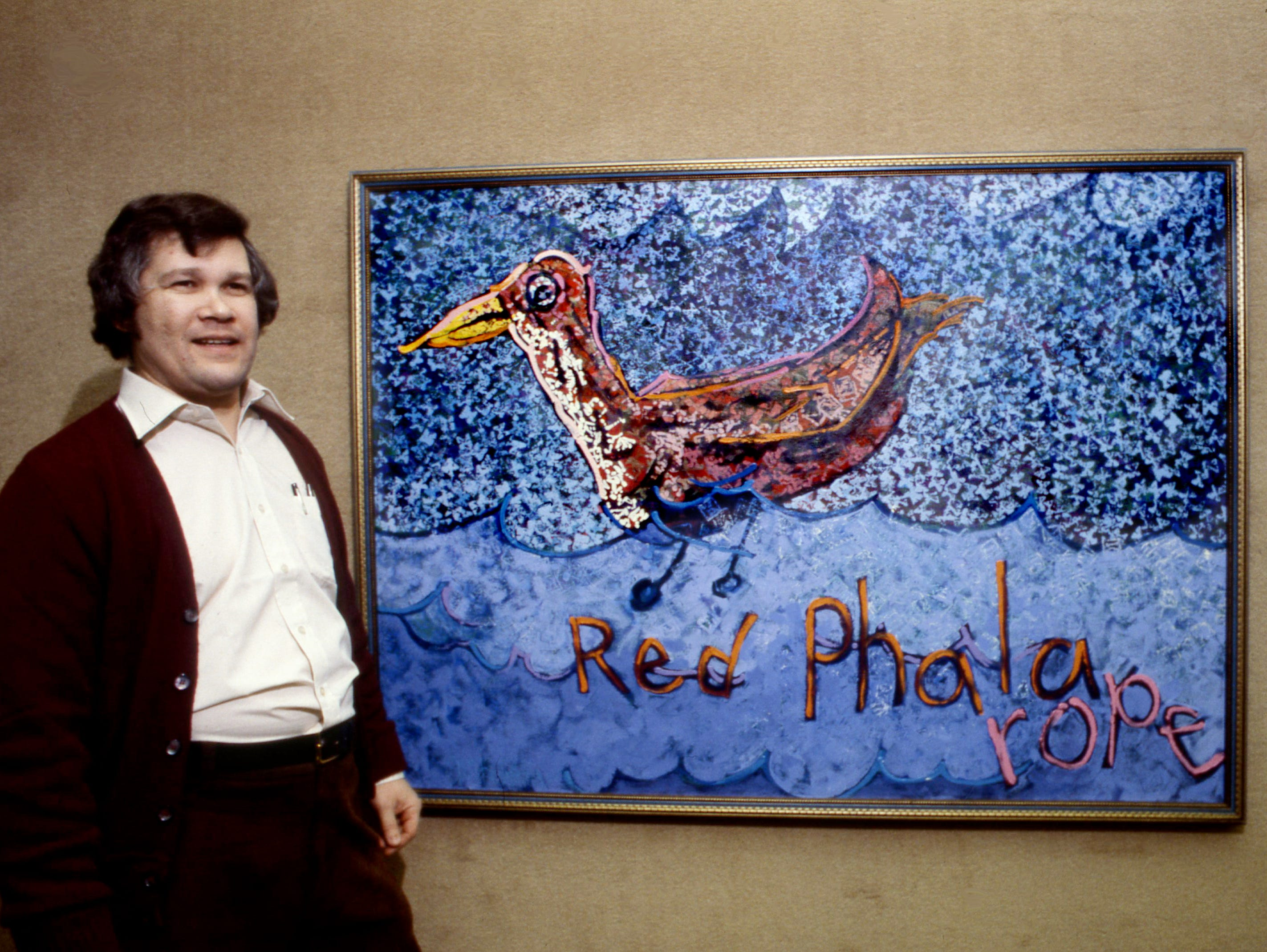 """Max Hochstetler, associate professor of art at Austin Peay State University, stands in front of his large painting inspired by his son's drawing Feb. 6, 1979. Son Andy, 9, drew the red phalarope and the lettering that his father used in his painting, which is in the show """"Images from My House"""" at APSU's Trahern Gallery in Clarksville."""