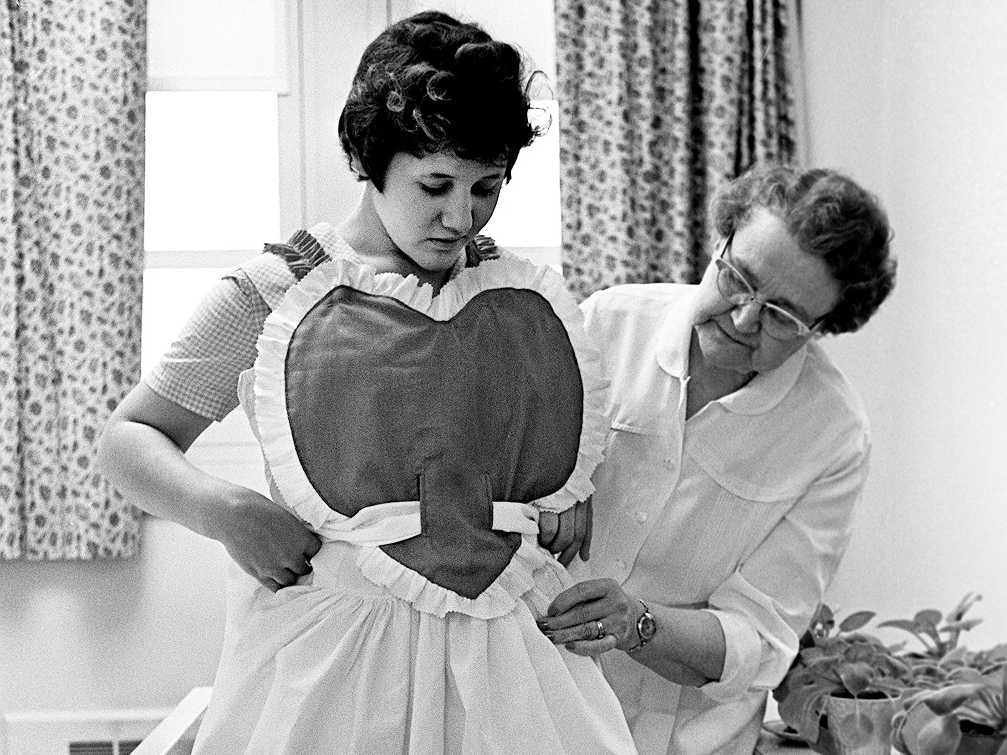 Staff nurse Lillian Welch, right, helps Shirley Chapman try on one of the costumes members of the sewing department at the State Vocational School for Girls made for the annual Valentine pageant and dance Feb. 8, 1961. The dance at the school in Tullahoma is one event where girls can dress to their hearts content.