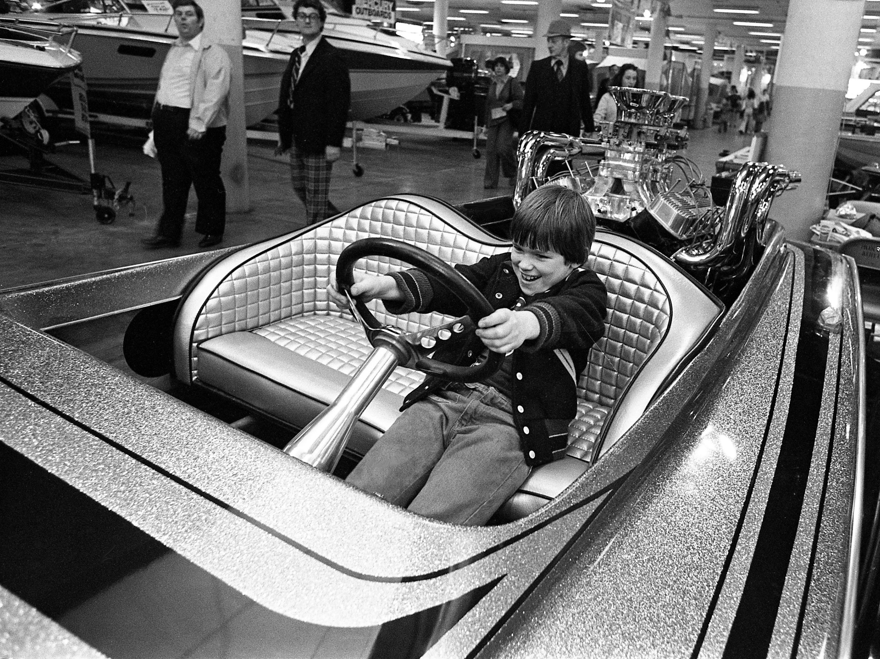 Cayce Joe Cobb, 8, son of Mr. and Mrs. Robert Cobb of Nashville, just may have lead feet as he gets the feel of this high-powered speedboat during the 23rd annual Great Lakes of the South Outdoor show at the Municipal Auditorium on Feb. 15, 1979.