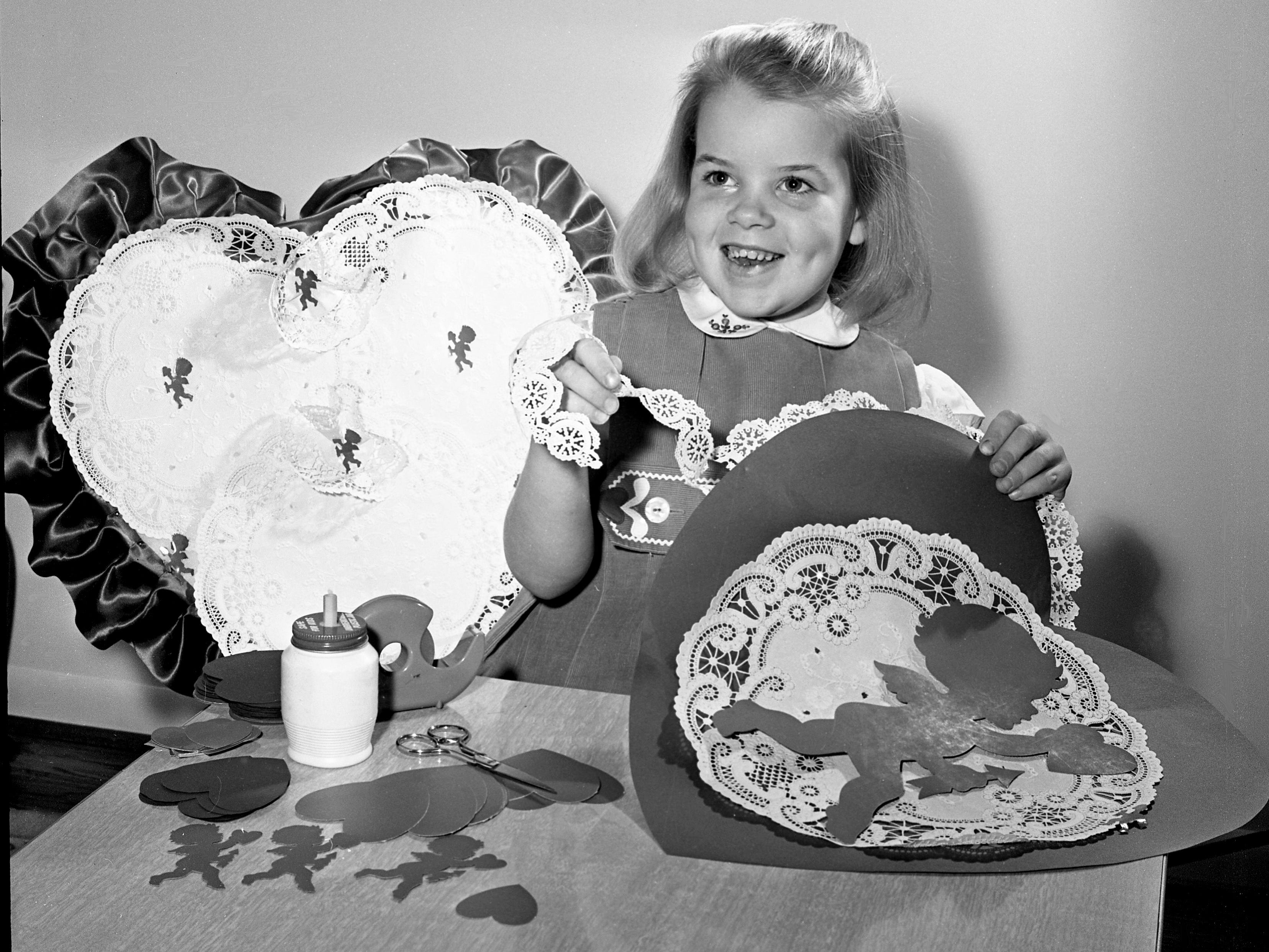 Lacey frills are used to trim the valentine Linda Evers is making Feb. 6, 1964. But Linda wouldn't tell for whom she intended the pretty heart-shaped card.