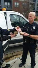 Officer Frank Campbell assists a lost chicken in downtown Nashville.