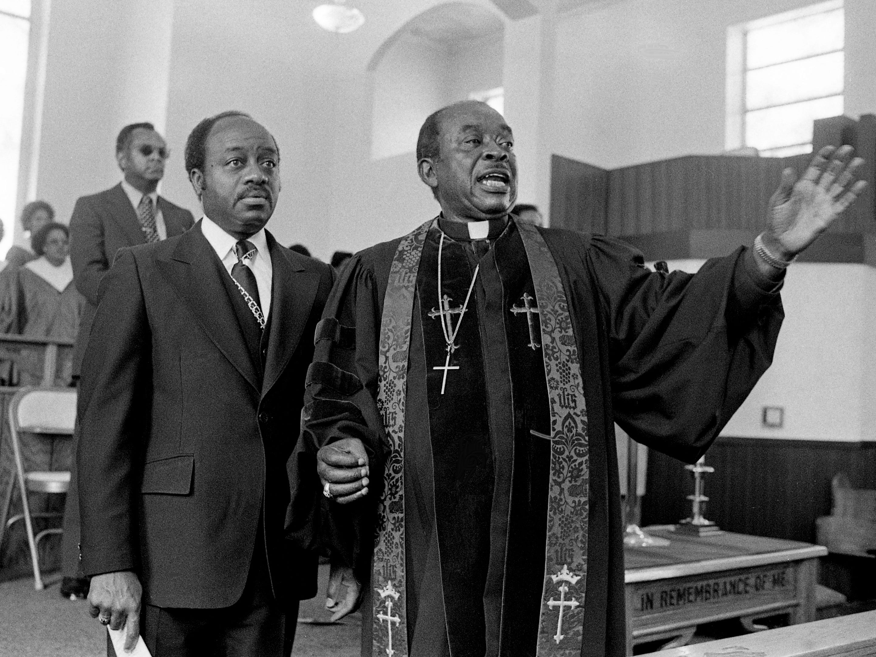"""Bishop William F. Ball, right, presiding bishop of the 18th Episcopal District of the AME Church, gives the """"Invitation to Discipleship"""" at the Lee Chapel AME Church as the church's Rev. Charles A. Jones looks on Feb. 11, 1979."""