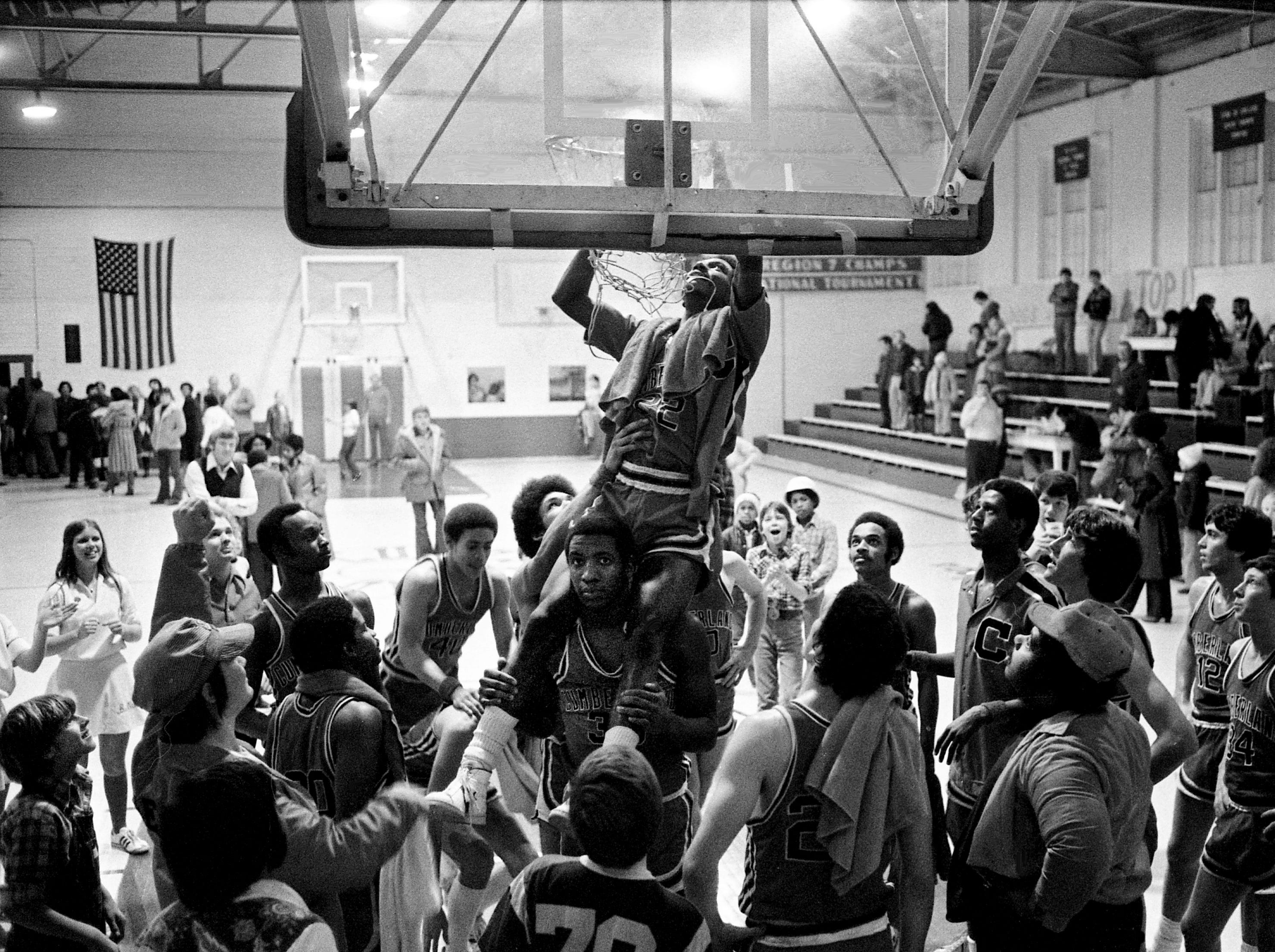 On the shoulders of a teammate, Wendall Bates helps to cut down the net as teammates and fans join in the celebration of Cumberland College's 111-83 win over Chattanooga at home in Lebanon on Feb. 10, 1979. The Bulldogs captured the TJCAA's Eastern Division championship title.