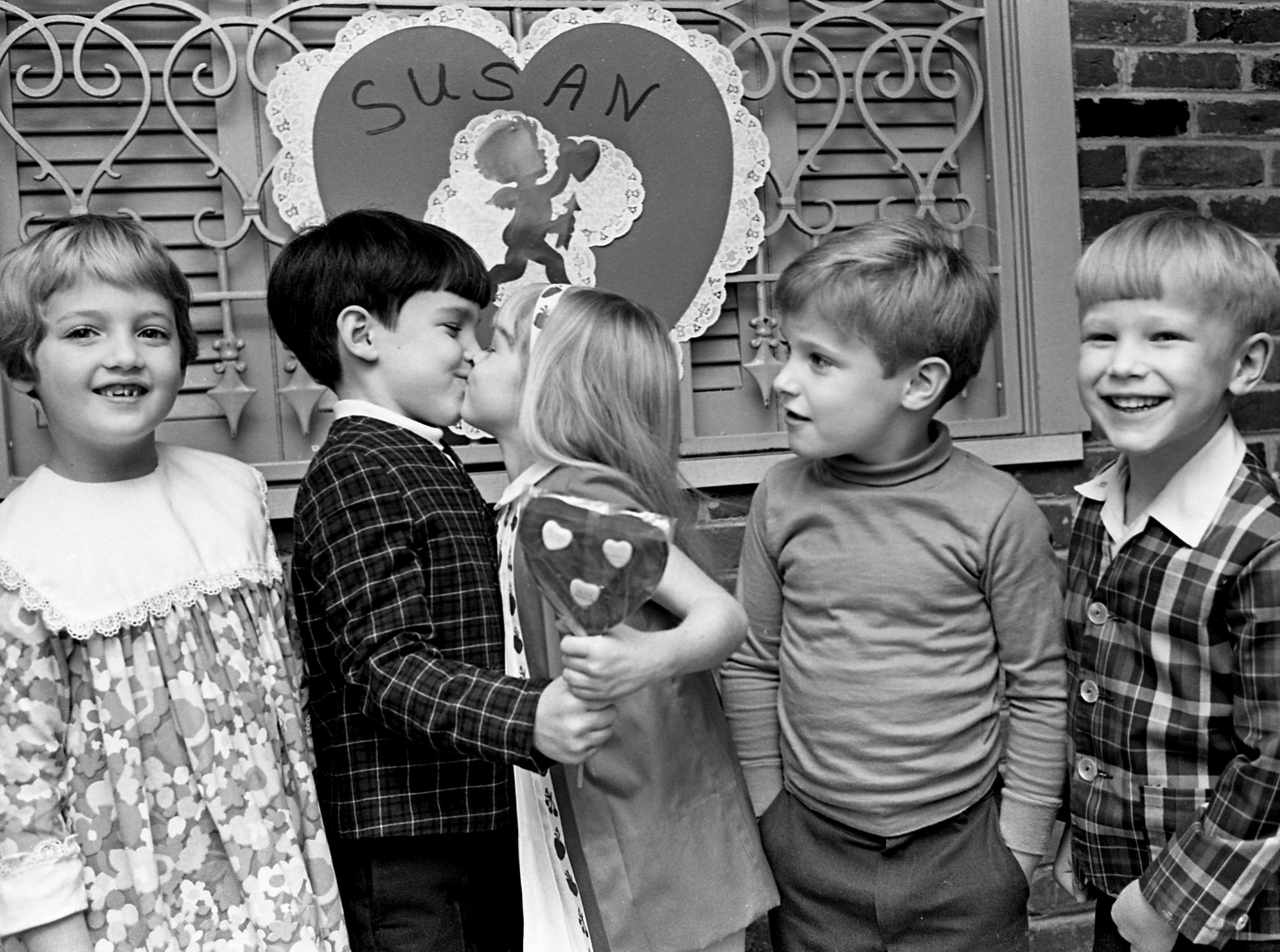 Susan Shreeve, center, was guest of honor at a Valentine party given by her mother, Mrs. George Shreeve, at the Seven Hills Club on Feb. 8, 1968. Susan is receiving a valentine kiss and gift from Tim Werthan, second from left, as Joan Richard, left, Taft Garrett and Johnny Mills look on.