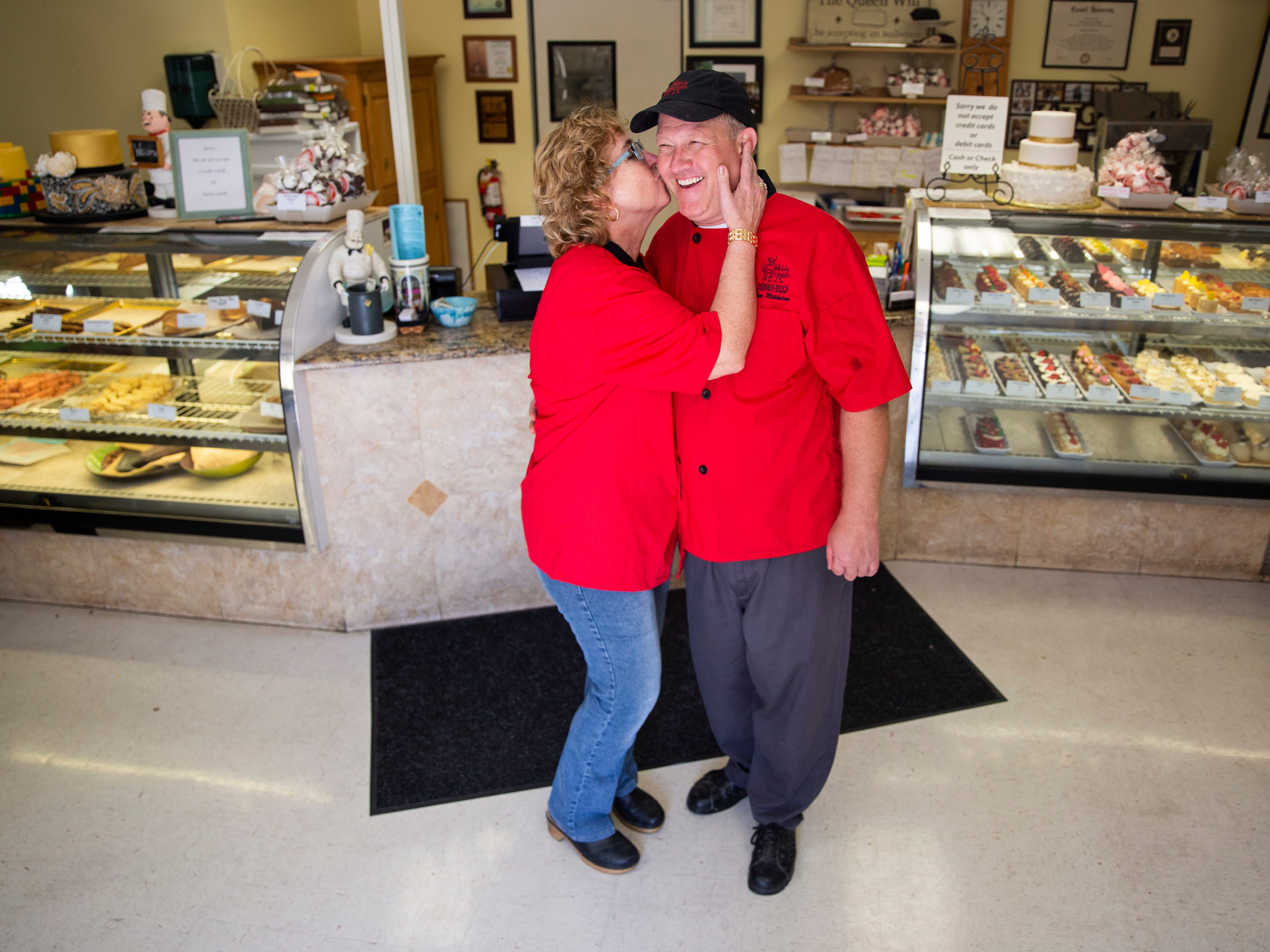 Elizabeth Mikkelsen kisses her husband and business partner, Paw Mikkelsen, on the cheek at Mikkelsen's Pastry Shop in North Naples on Thursday, Feb. 7, 2019.