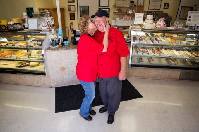 Elizabeth Mikkelsen kisses her husband and business partner, Paw Mikkelsen, on the cheek at Mikkelsen's Pastry Shop in North Naples on Thursday, Feb. 7, 2019.