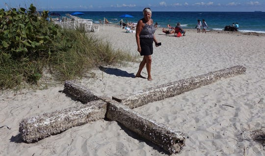 Aglair Rigos checks out a cross  on the Galt Ocean Mile behind the Ocean Manor Beach Resort, in Fort Lauderdale on Tuesday, Feb. 5, 2019.  The large, barnacle-covered wooden cross washed ashore along the South Florida beach, captivating tourists who dragged it from the water's edge.