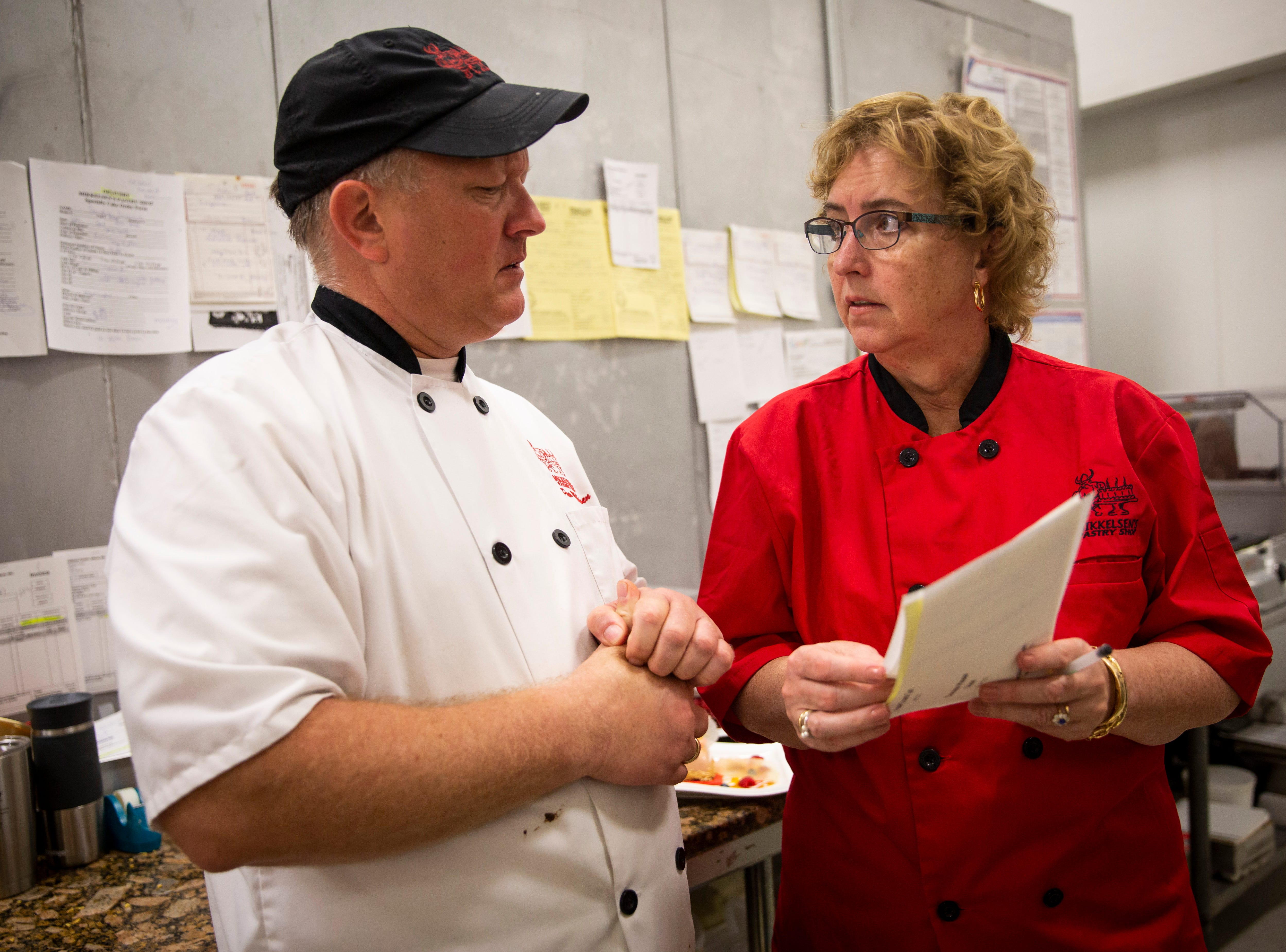Elizabeth Mikkelsen asks Paw Mikkelsen about an order at Mikkelsen's Pastry Shop in North Naples on Thursday, Feb. 7, 2019. Typically Elizabeth handles retail orders and front-of-house business, while Paw takes care of ordering ingredients, communicating with chefs at area clubs and directing employees in the kitchen.