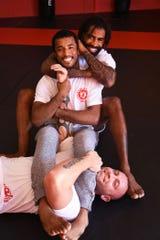 Evolution Mixed Martial Arts' new Muay Thai/ Kickboxing head coach Cosmo Alexandre, rear, owner Keith Rummel, bottom, and jiu jitsu coach Orlando Castillo.