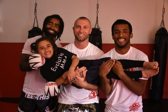 Evolution Mixed Martial Arts' new Muay Thai/ Kickboxing head coach Cosmo Alexandre, from left, owner Keith Rummel, and jiu jitsu coach Orlando Castillo, with Leia Castillo, 6.
