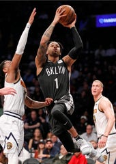 Brooklyn Nets guard D'Angelo Russell (1) goes up for a shot as Denver Nuggets guard Monte Morris, left. defends and forward Mason Plumlee watches during the second half of an NBA basketball game Wednesday, Feb. 6, 2019, in New York. The Nets defeated the Nuggets 135-130.