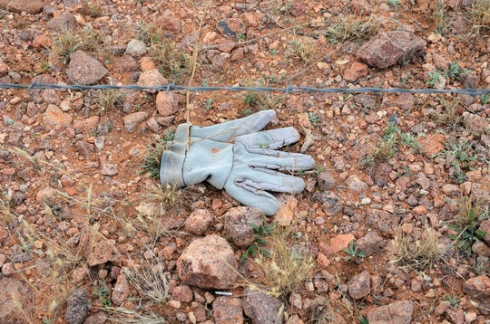 A glove lies on the ground beside Russell Johnson's barbed wire fence that separates Mexico from his New Mexico property.